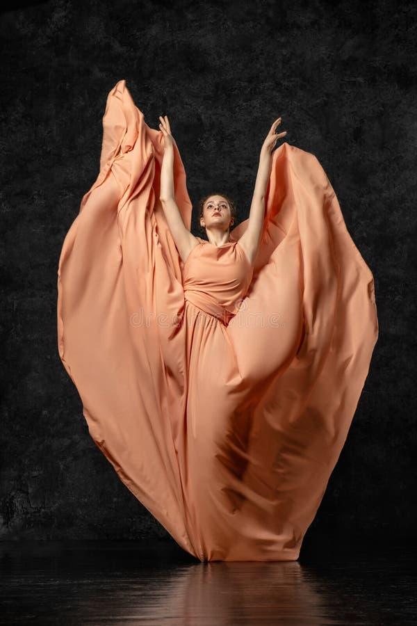 Молодой грациозный танцор стоя против предпосылки черная стена одетая в длинном платье персика, стоя в представлении бабочки стоковое фото rf