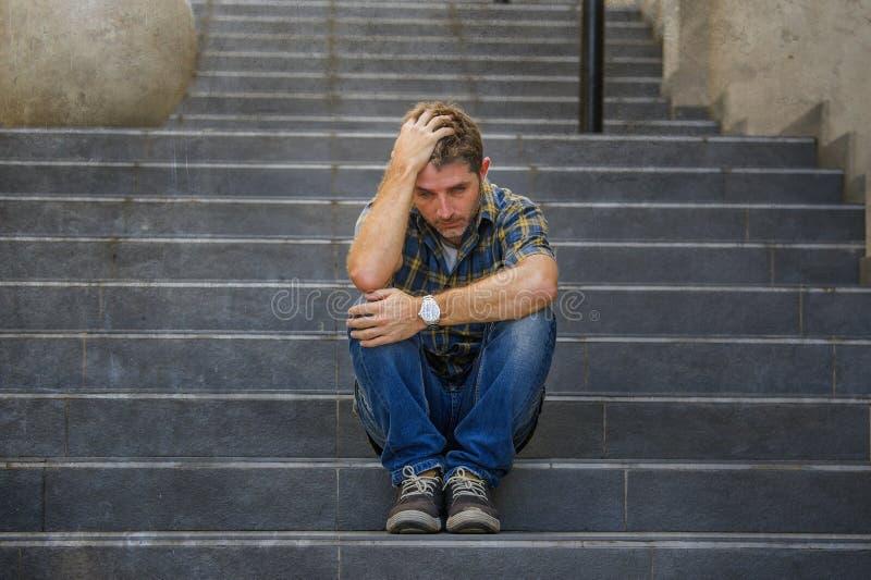 Молодой грустный и отчаянный человек сидя outdoors на лестницах улицы страдая плакать чувства тревожности и депрессии жалкий внут стоковое изображение rf