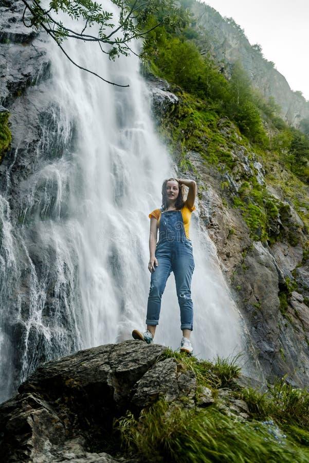 Молодой девочка-подросток стоя на большом каменном близко водопаде стоковые фото