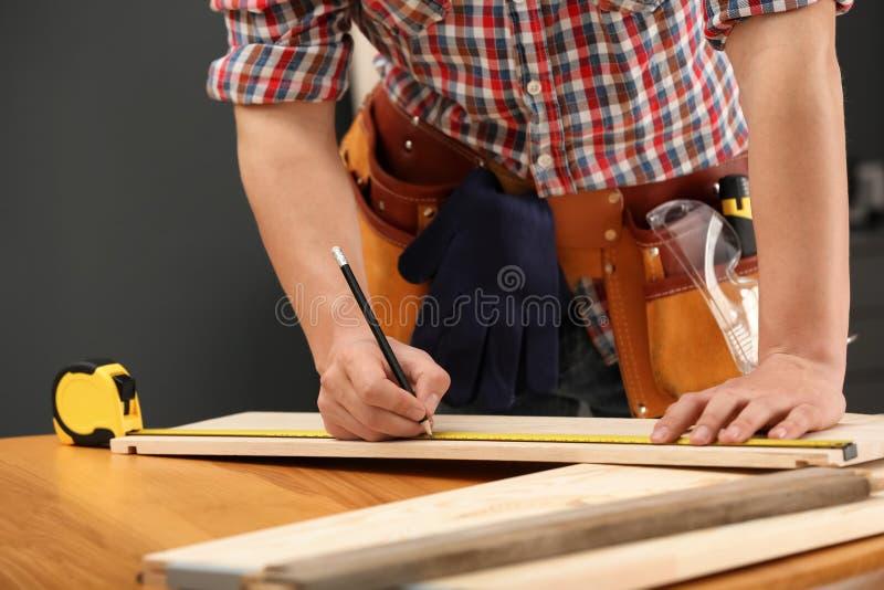 Молодой деятеля делая метки на тимберсе внутри помещения Домашний ремонт стоковое фото rf