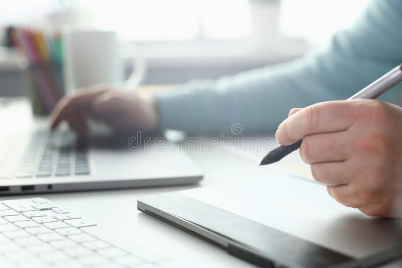 Молодой дизайнер держит ручку от планшета в его стоковое фото