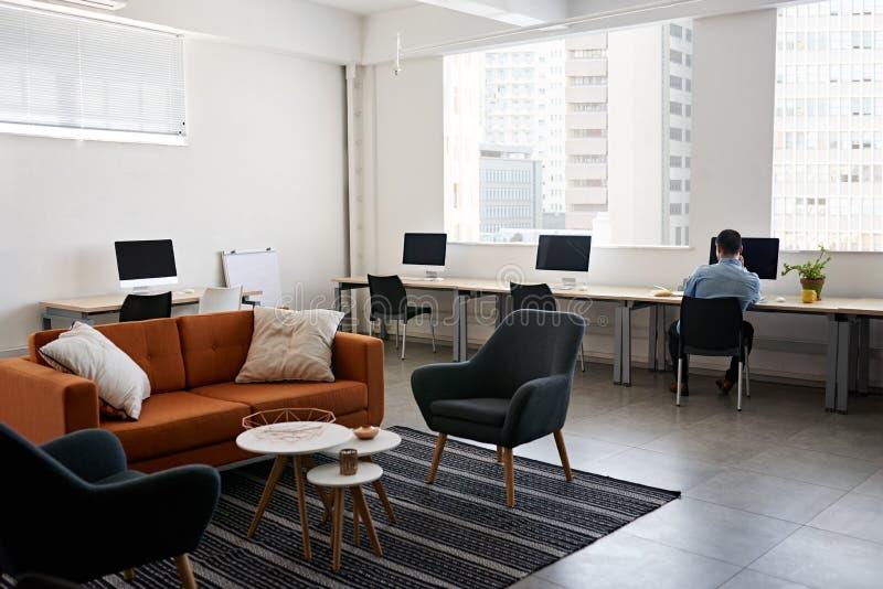 Молодой дизайнер работая самостоятельно в современном офисе стоковая фотография rf