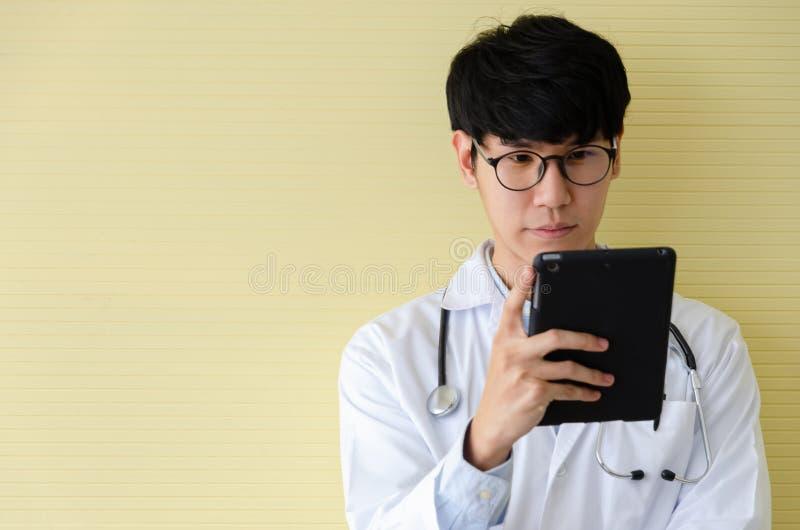 Молодой доктор в белой форме выглядя серьезный на цифровом планшете стоковые изображения rf