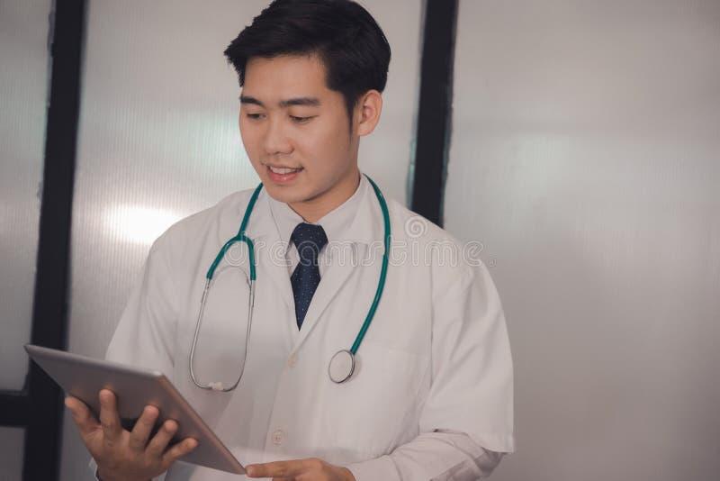 Молодой доктор держа таблетку на больнице практикующий врач читая da стоковое изображение rf