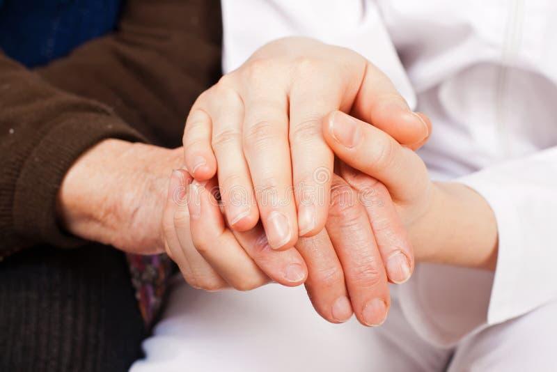 Молодой доктор держит пожилые руки женщины стоковая фотография