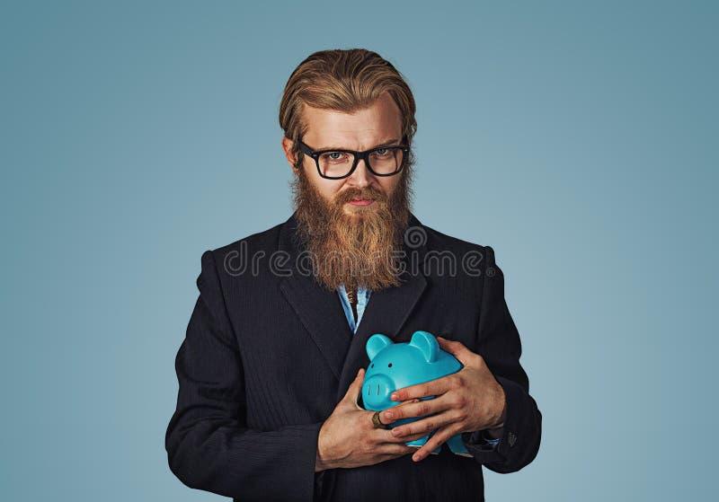 Молодой жадный скупой бизнесмен держа копилку стоковая фотография