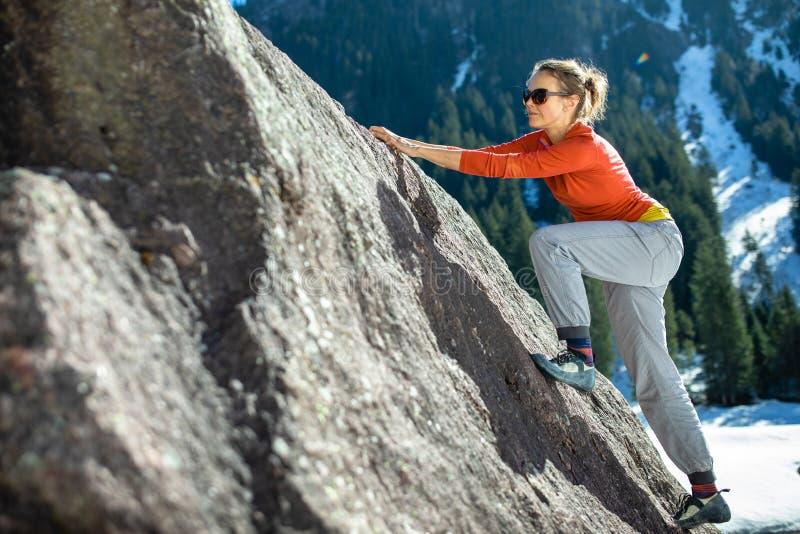 Молодой женский альпинист на естественном валуне outdoors стоковое изображение