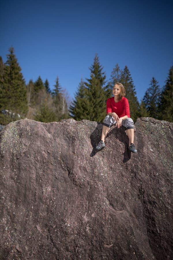 Молодой женский альпинист на естественном валуне outdoors стоковая фотография