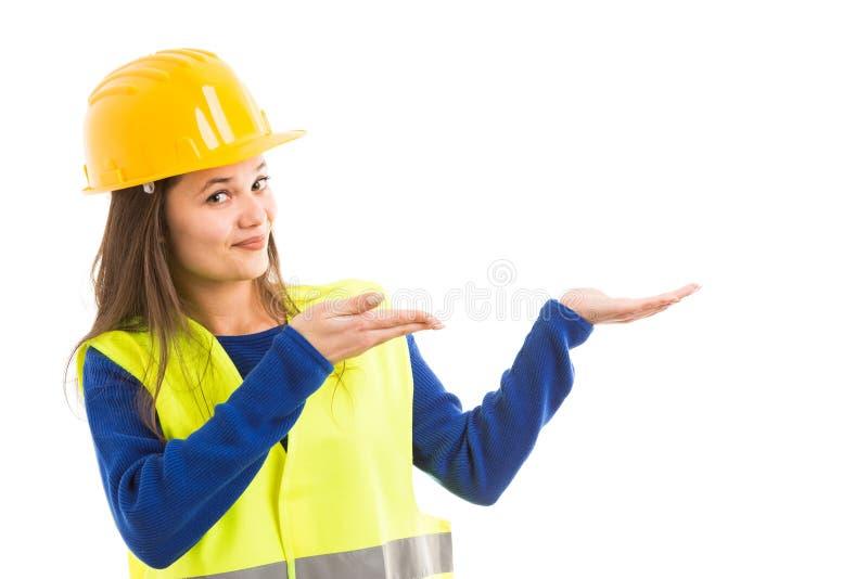 Молодой женский архитектор делая жест представления стоковые фото