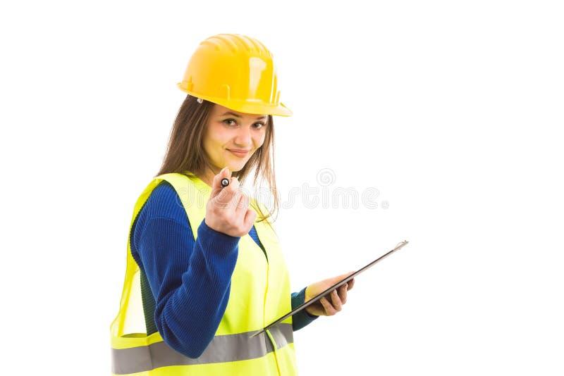 Молодой женский архитектор держа доску сзажимом для бумаги стоковое изображение rf