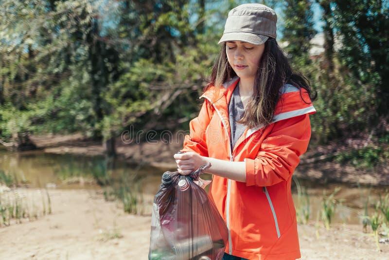 Молодой женский волонтер собирает отброс и пластиковые бутылки около реки в сумке отброса Концепция дня земли и стоковые фото