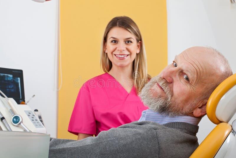 Молодой женский дантист с пожилым пациентом стоковые изображения