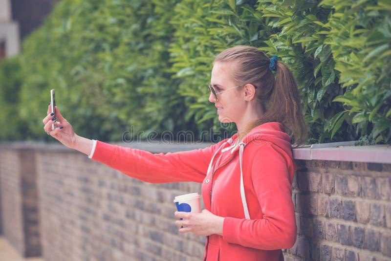 Молодой женский держа кофе, который нужно пойти принимать selfie в парке стоковая фотография rf