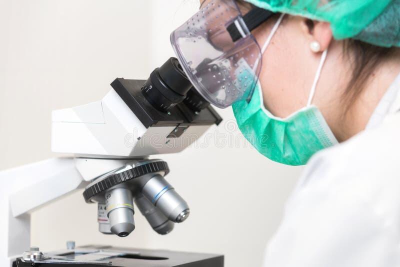 Молодой женский доктор работая с микроскопом в лаборатории, защищенной против biohazard с маской, шляпой, и стеклами стоковое фото