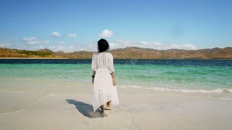 Молодой женский идти к пляжу стоковое фото