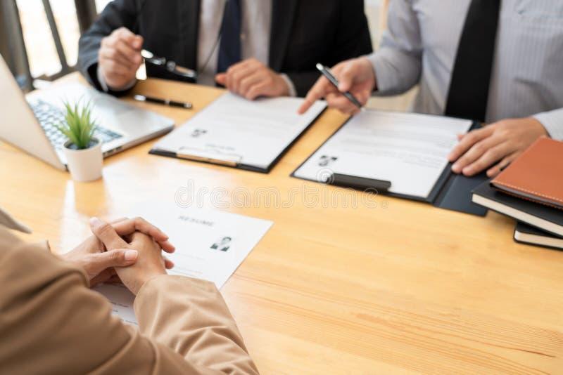 Молодой женский кандидат бизнес-леди в менеджере офиса мужском интервьюируя держащ резюме и говорящ к работодателю, собеседованию стоковое фото