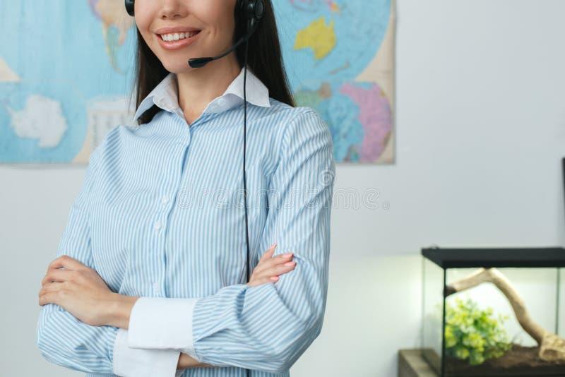 Молодой женский консультант агента по путешествиям в конце-вверх шлемофона агенства путешествия нося стоковое фото rf