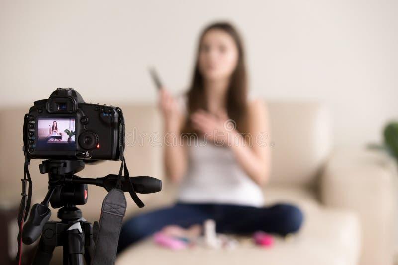 Молодой женский обзор продукта записи videoblogger для блога стоковое фото rf