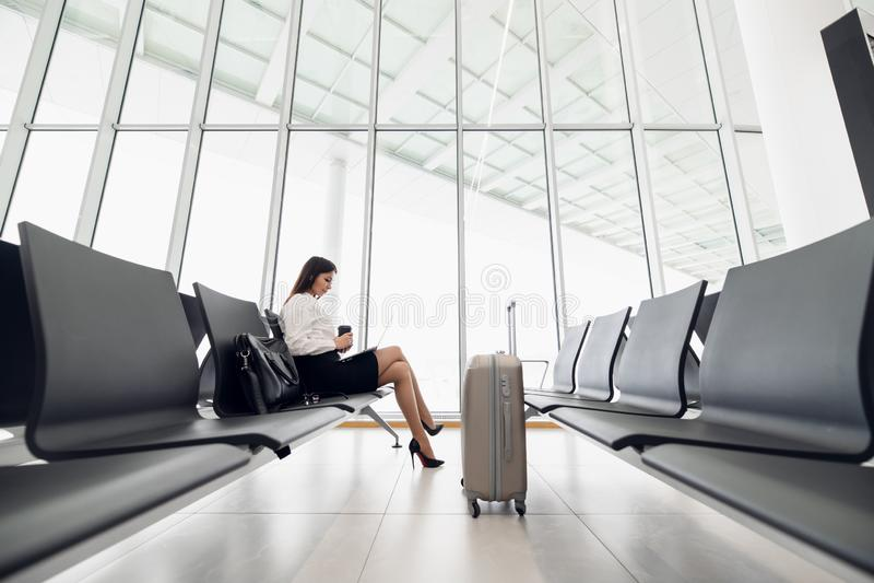 Молодой женский пассажир в аэропорте, используя ее планшет пока ждущ ее полет стоковое фото