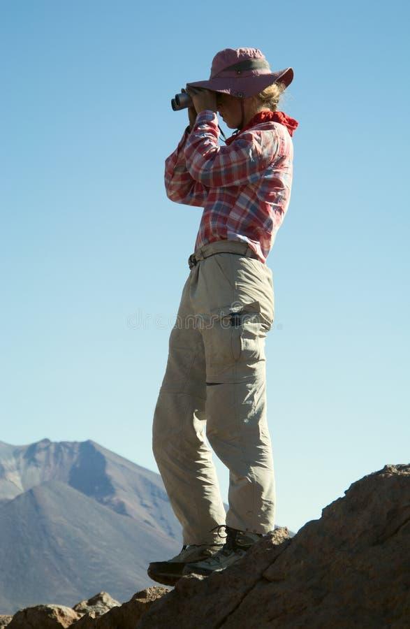 Молодой женский путешественник использует бинокли в горах стоковое фото