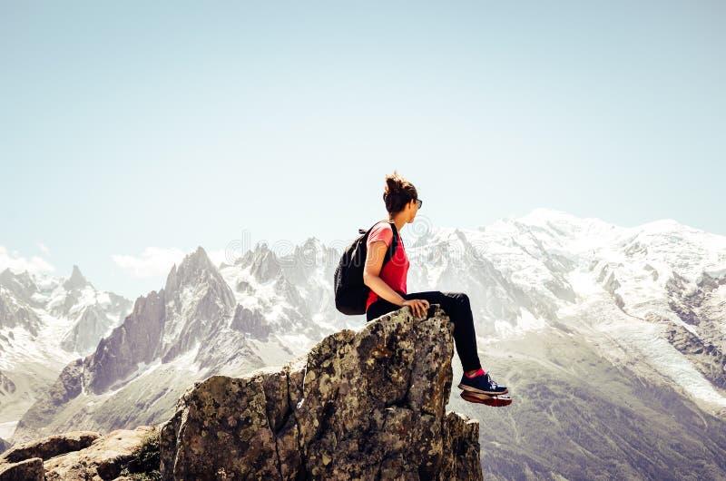 Молодой женский путешественник сидя на краю утесов Высокие горы в предпосылке Укладывать рюкзак женщины Приключение Активный стоковое фото rf