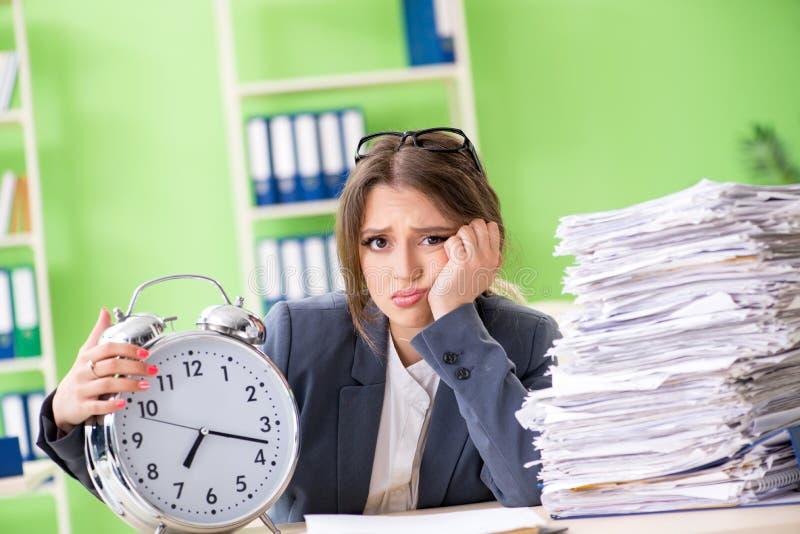 Молодой женский работник очень занятый с продолжающийся обработкой документов во времени m стоковое изображение rf