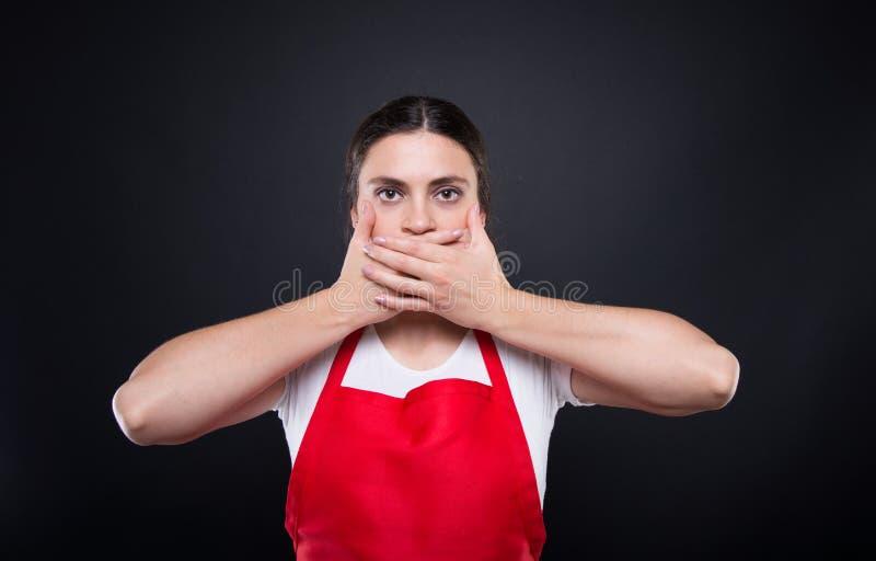 Молодой женский работник покрывая закрытый рот с руками стоковые изображения rf