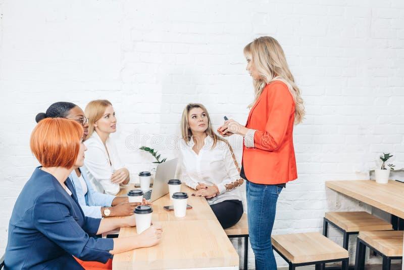 Молодой женский специалист делает представление на встрече в офисе стоковое изображение rf