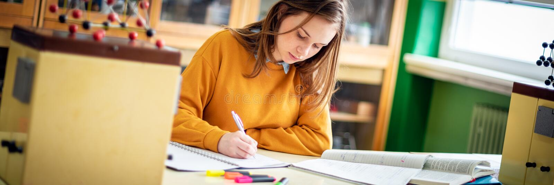 Молодой женский студент колледжа в классе химии, писать примечания Сфокусированный студент в классе Знамя сети концепции образова стоковая фотография