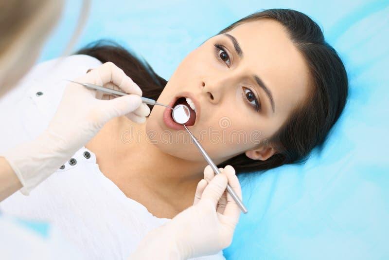 Молодой женский терпеливый посещая офис дантиста Красивые страх и боль чувства женщины во время доктора работая на зубах стоковое изображение rf