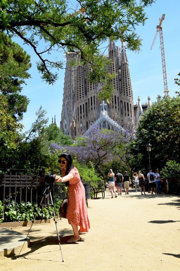 Молодой женский турист исправляя установки на камере с Ла Sagrada Familia на заднем плане стоковые фото