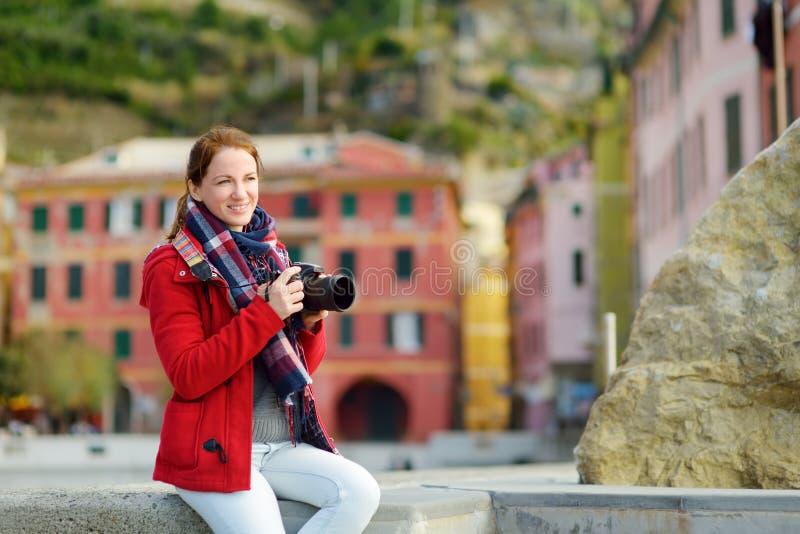 Молодой женский турист наслаждаясь взглядом Vernazza, одной из 5 столети-старых деревень Cinque Terre, расположенных на изрезанно стоковые фото