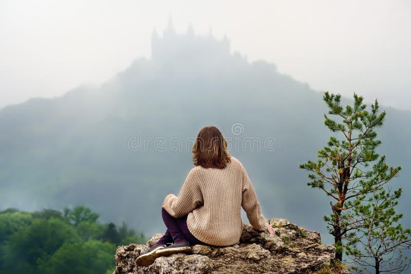 Молодой женский турист смотря на известном замке Hohenzollern в сильном тумане, Германии стоковая фотография rf