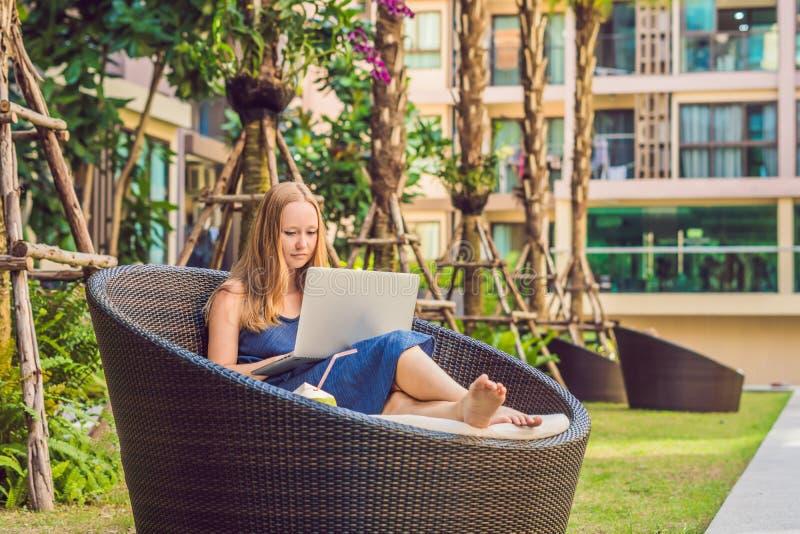 Молодой женский фрилансер сидя около бассейна с ее ноутбуком Занятый на праздниках Дистантная концепция работы Скопируйте космос  стоковые фотографии rf