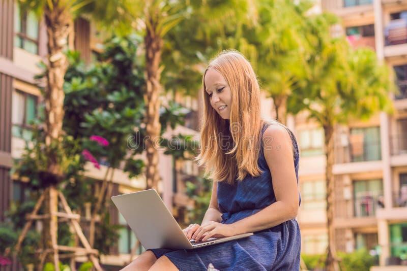 Молодой женский фрилансер сидя около бассейна с ее ноутбуком Занятый на праздниках Дистантная концепция работы Скопируйте космос  стоковое изображение
