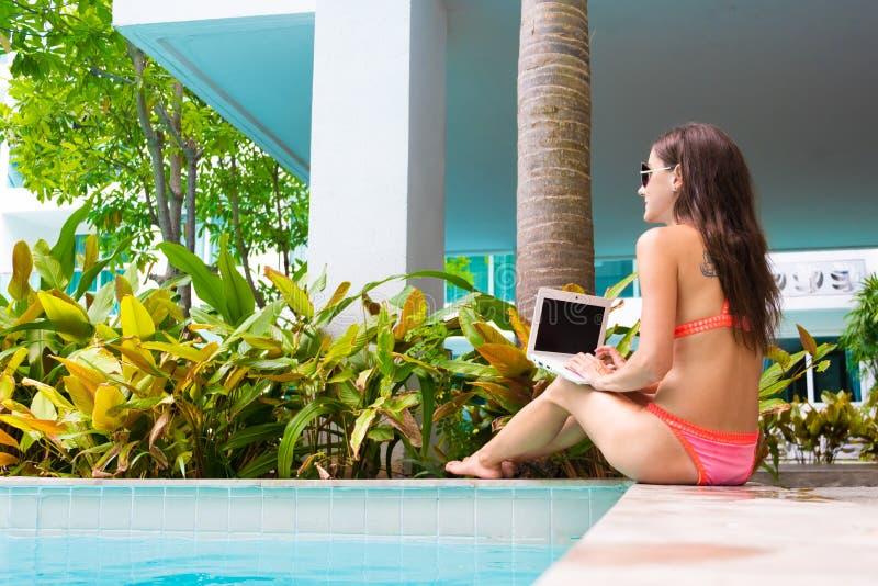 Молодой женский фрилансер сидя с ноутбуком около бассейна E Занятый во время праздников Концепция удаленной работы стоковое фото