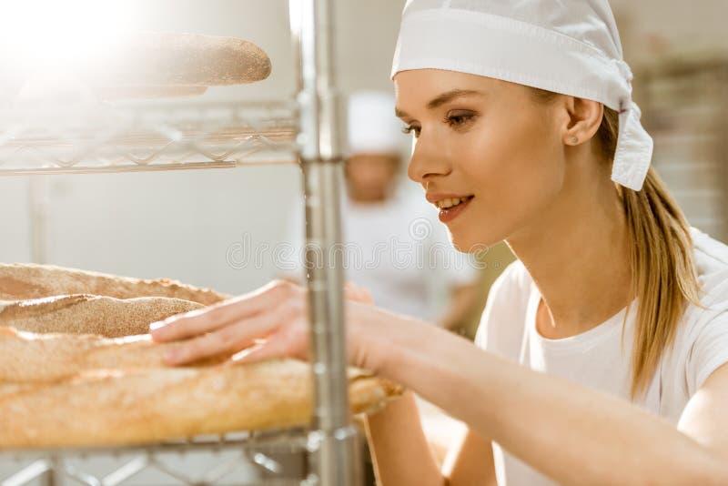 молодой женский хлебопек делая рассмотрение свеже испеченных хлебцев хлеба стоковая фотография