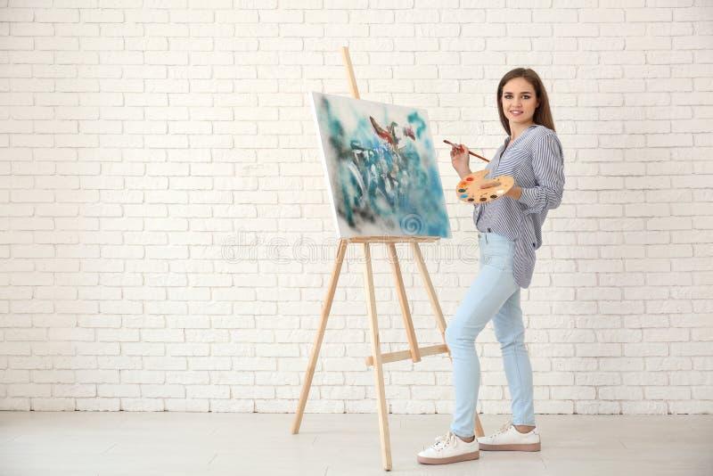 Молодой женский художник с мольбертом чертежа против белой кирпичной стены стоковое фото rf