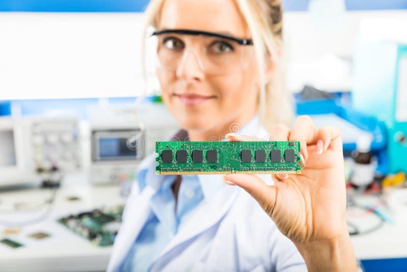 Молодой женский электронный инженер держа модуль памяти в руке стоковые фото