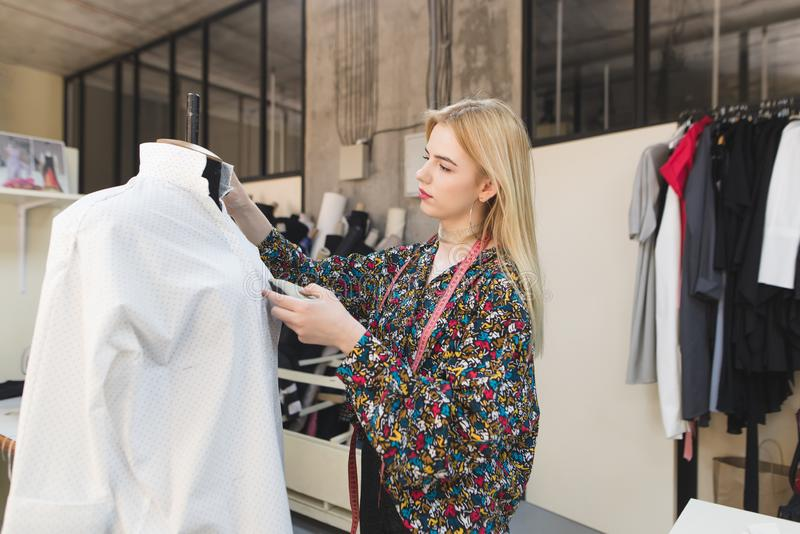 Молодой женский dressmaker стоит в деланной маникюр студии и регулирует одежды стоковое изображение rf