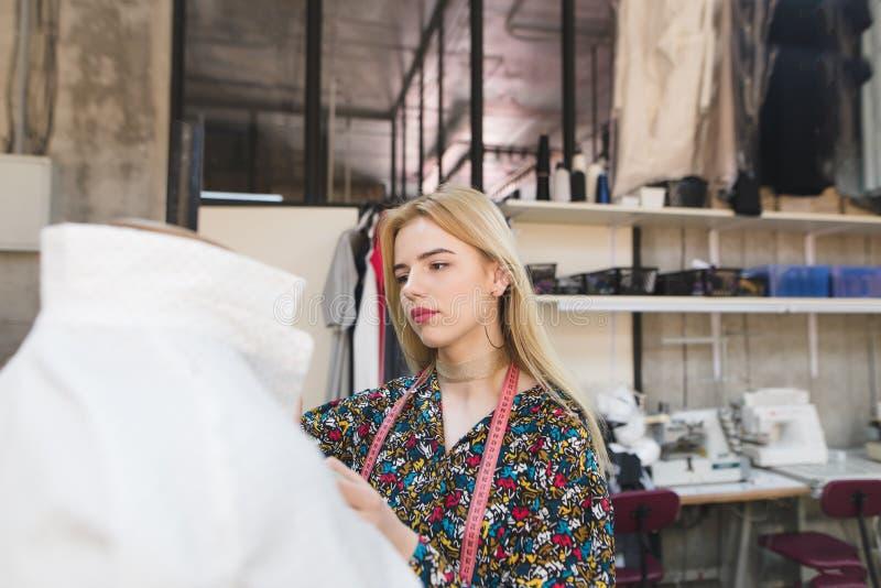 Молодой женский dressmaker стоит в деланной маникюр студии и регулирует одежды стоковое фото