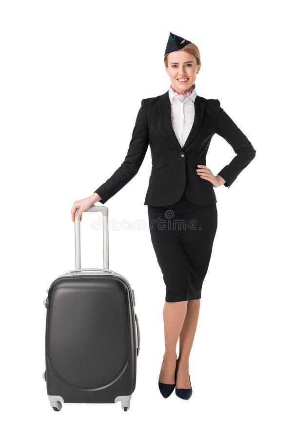 Молодой женский stewardess полагаясь на чемодане стоковые изображения rf