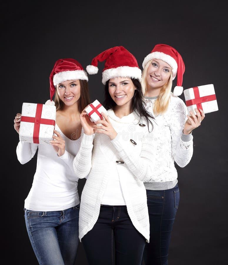 3 молодой женщины в костюме Санта Клауса с рождеством ходят по магазинам стоковое фото