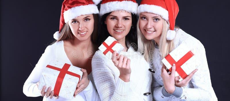 3 молодой женщины в костюме Санта Клауса с рождеством ходят по магазинам стоковые изображения