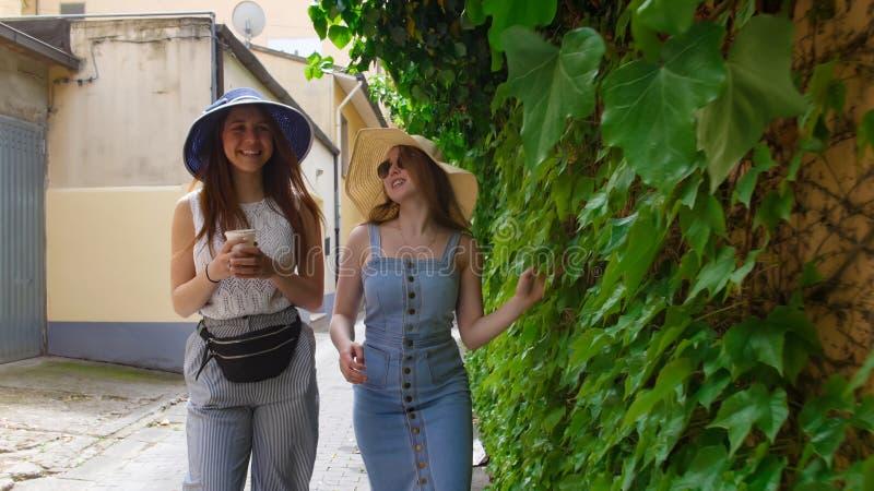 2 молодой женщины в panamas идя вдоль зеленой стены стоковое изображение rf