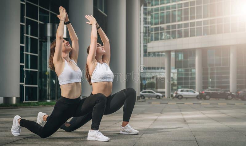 2 молодой женщины, девушки делая протягивающ тренировки, подогрев, делая йогу на улице города Разминка, укладывая на улицу города стоковые изображения