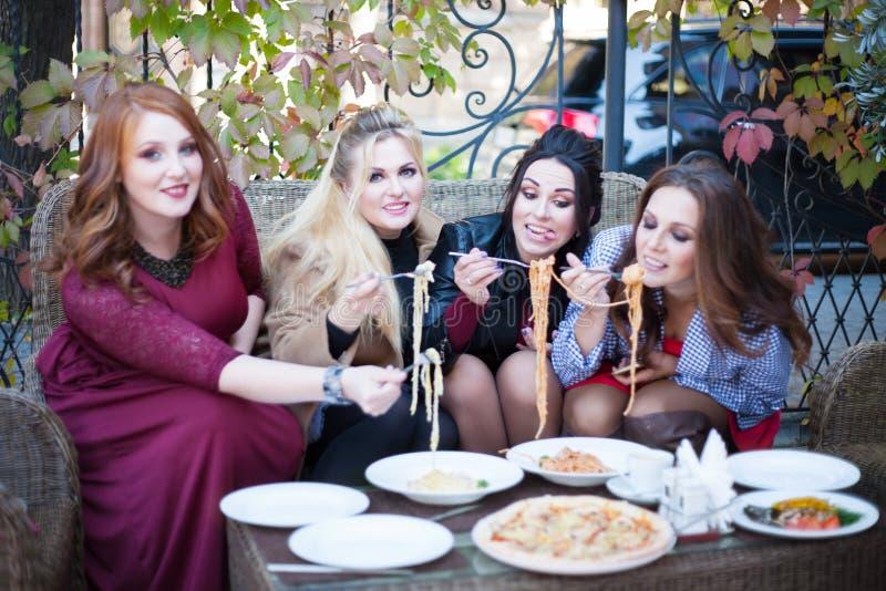 4 молодой женщины имея обед в кафе стоковое изображение
