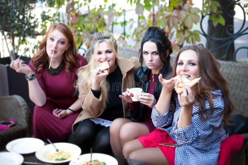 4 молодой женщины имея обед в кафе стоковые изображения rf