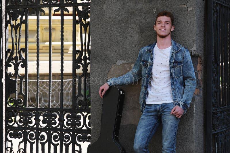 Молодой жизнерадостный парень с красными волосами на стробе с гитарой в случае стоковая фотография