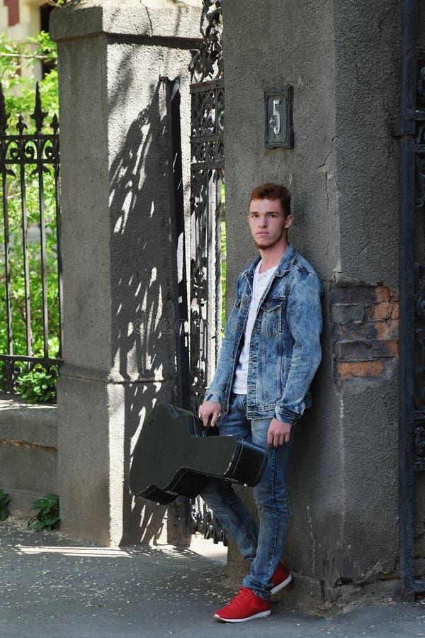 Молодой жизнерадостный парень с красными волосами на стробе с гитарой в случае стоковое изображение rf